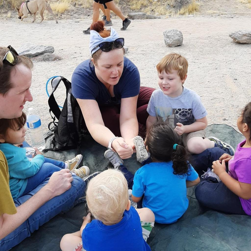A woman shows a rock to a group of children sitting in a circle.